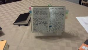 With A notebook propped up. So much easier to transcribe this way.